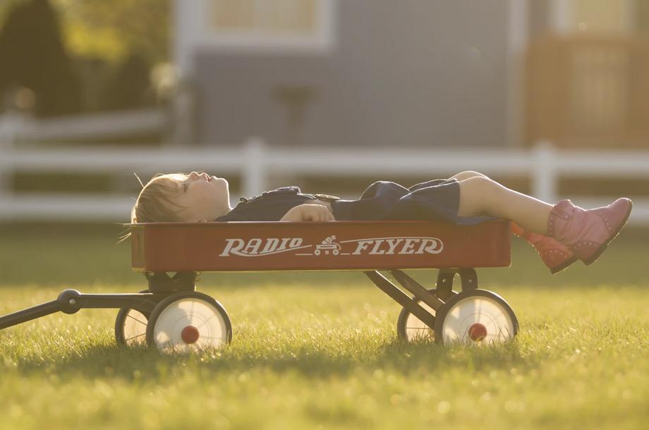 Young boy laying in Radio Flyer wagon photo | Mutual Insurance | Personal Insurance
