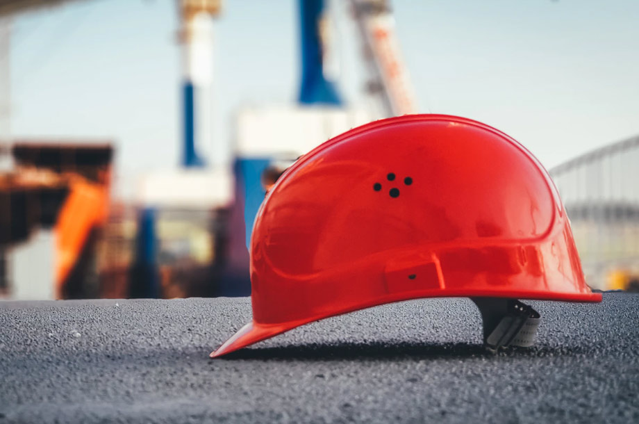 Red hard hat sitting on pavement photo | Mutual Insurance | Workers' Compensation